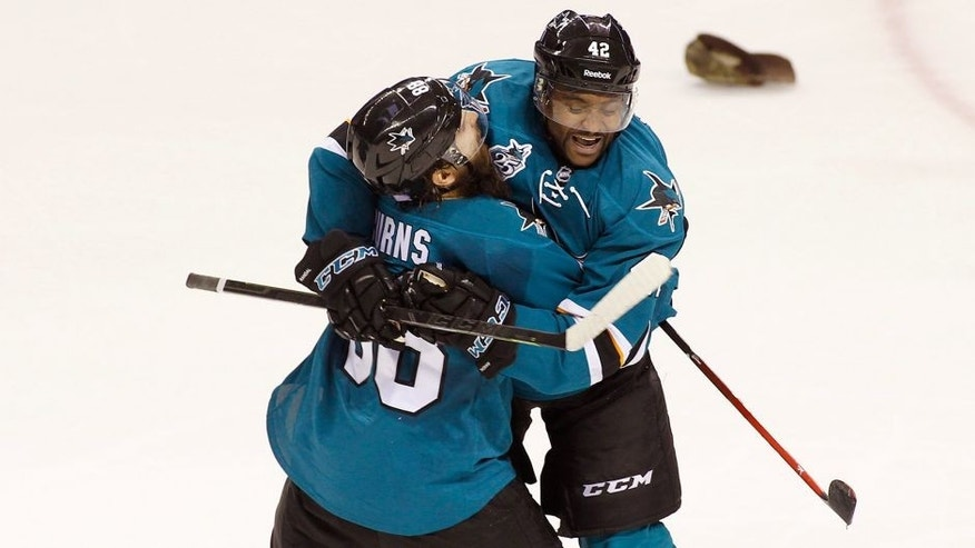 San Jose Sharks' Joel Ward, right, celebrates with teammate Brent Burns after scoring his third goal of the game for a hat trick against the Carolina Hurricanes during the third period of an NHL hockey game, Saturday, Oct. 24, 2015, in San Jose, Calif. (AP Photo/George Nikitin)