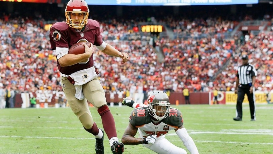 Washington Redskins quarterback Kirk Cousins (8) carries the ball into the end zone for a touchdown on a quarterback keeper as Tampa Bay Buccaneers free safety Bradley McDougald (30) looks on during the first half of an NFL football game in Landover, Md., Sunday, Oct. 25, 2015. (AP Photo/Patrick Semansky)