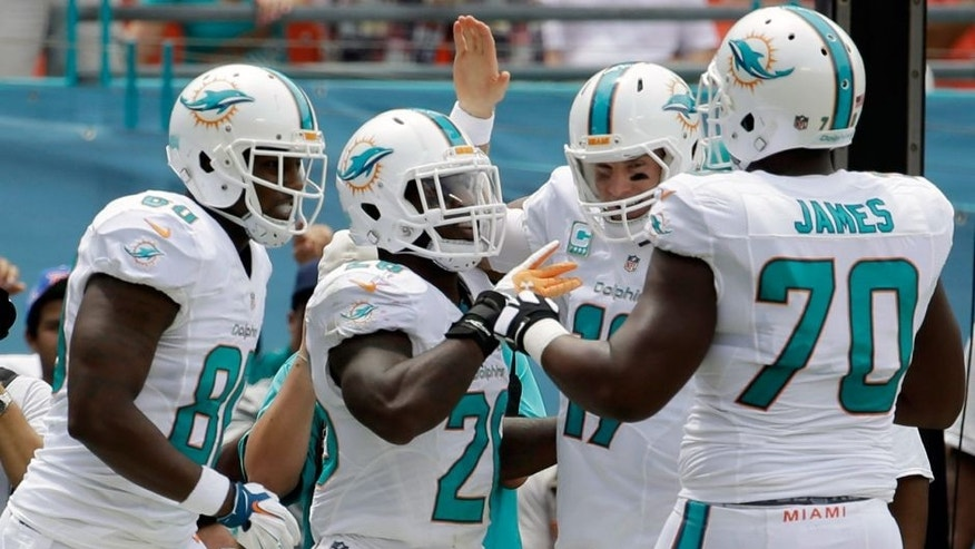 Miami Dolphins running back Lamar Miller, second from left, is congratulated by tight end Dion Sims, left, quarterback Ryan Tannehill, second from right, and offensive tackle Ja'Wuan James (70) after Miller scored a touchdown during the first half of an NFL football game against the New England Patriots, Sunday, Sept. 7, 2014, in Miami Gardens, Fla. (AP Photo/Lynne Sladky)