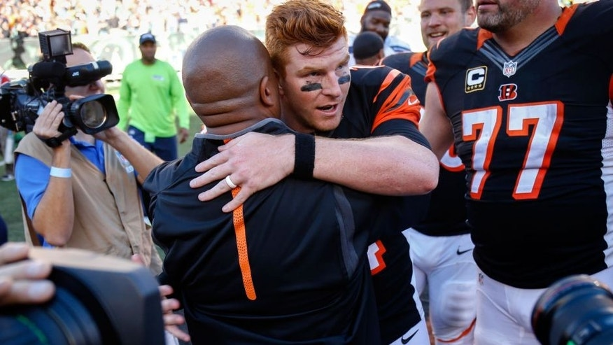 Cincinnati Bengals quarterback Andy Dalton, center right, hugs offensive coordinator Hue Jackson after an NFL football game against the Seattle Seahawks, Sunday, Oct. 11, 2015, in Cincinnati. The Bengals won 27-24. (AP Photo/Gary Landers)