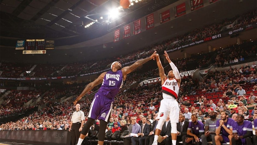 PORTLAND, OR - OCTOBER 5: Damian Lillard #0 of the Portland Trail Blazers shoots against DeMarcus Cousins #15 of the Sacramento Kings during the preseason game on October 5, 2015 at the Moda Center Arena in Portland, Oregon. NOTE TO USER: User expressly acknowledges and agrees that, by downloading and or using this photograph, user is consenting to the terms and conditions of the Getty Images License Agreement. Mandatory Copyright Notice: Copyright 2015 NBAE (Photo by Sam Forencich/NBAE via Getty Images)