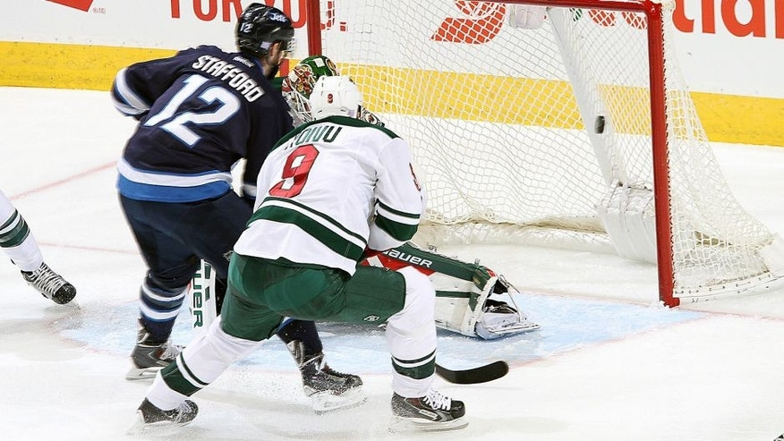 <p>WINNIPEG, MB - OCTOBER 25: Drew Stafford #12 of the Winnipeg Jets chips the puck into the net for a second period goal against the Minnesota Wild at the MTS Centre on October 25, 2015 in Winnipeg, Manitoba, Canada. (Photo by Darcy Finley/NHLI via Getty Images)</p>