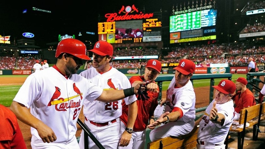 Sep 1, 2015; St. Louis, MO, USA; St. Louis Cardinals shortstop Jhonny Peralta (27) is congratulated by manager Mike Matheny (26), bench coach David Bell (25) and hitting coach John Mabry (47) after scoring against the Washington Nationals during the third inning at Busch Stadium. Mandatory Credit: Jeff Curry-USA TODAY Sports