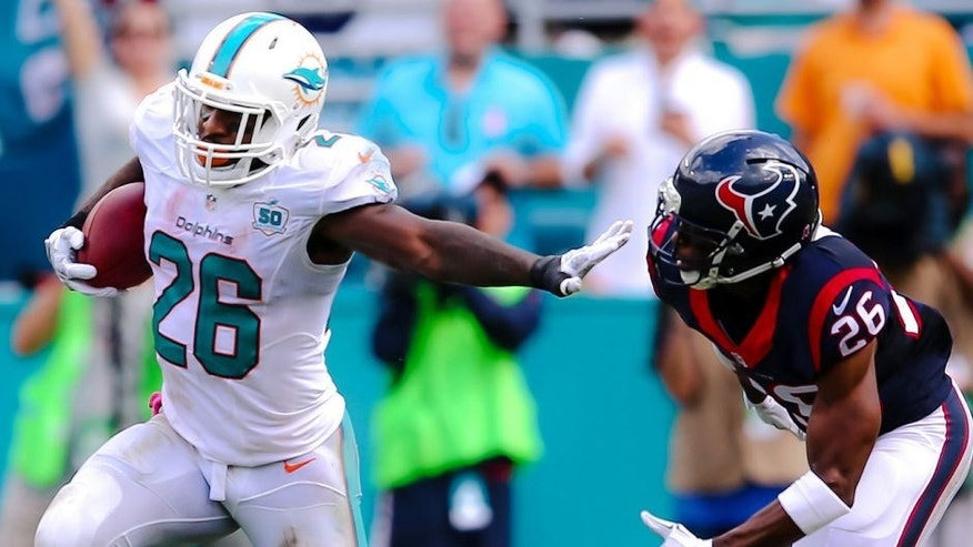 Oct 25, 2015; Miami Gardens, FL, USA; Miami Dolphins running back Lamar Miller (26) carries the ball past Houston Texans defensive back Rahim Moore (26) during the first half at Sun Life Stadium. Mandatory Credit: Steve Mitchell-USA TODAY Sports