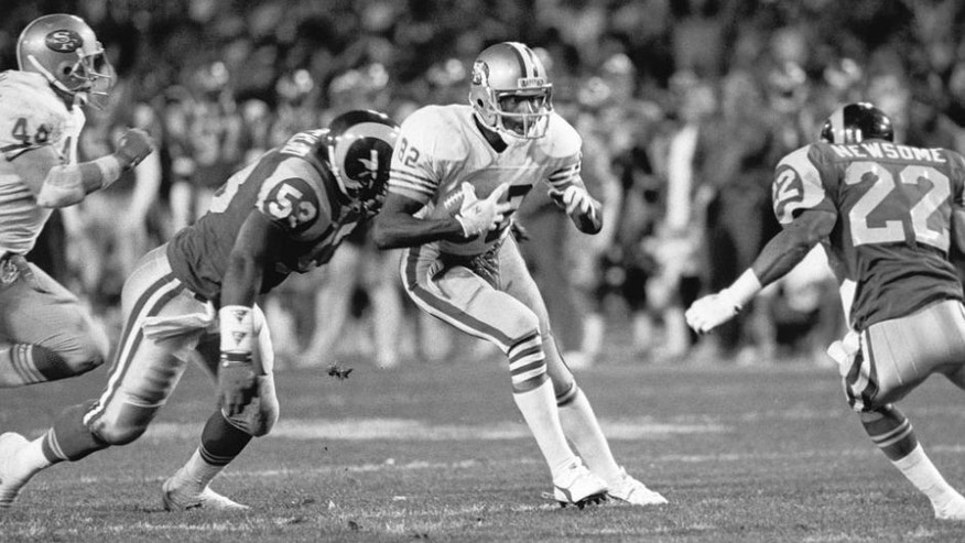 ANAHEIM, CA - DECEMBER 11: Wide receiver John Taylor #82 of the San Francisco 49ers evades linebacker Fred Strickland #53 and safety Vince Newsome #22 of the Los Angeles Rams during the game on December 11, 1989 at Anaheim Stadium in Anaheim, California. The 49ers won 30-27. (Photo by Michael Zagaris/Getty Images)