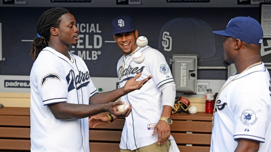 Jun 3, 2015; San Diego, CA, USA; San Diego Chargers player Melvin Gordon (left) juggles as Craig Mager (center) and Denzel Perryman watch before throwing out the ceremonial first pitch before the game between the New York Mets and San Diego Padres at Petco Park. Mandatory Credit: Jake Roth-USA TODAY Sports