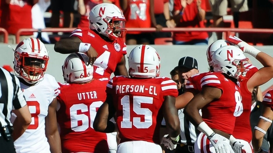 Oct 10, 2015; Lincoln, NE, USA; Teammates celebrate after Nebraska Cornhuskers quarterback Tommy Armstrong Jr. (4) scores against the Wisconsin Badgers at Memorial Stadium. Mandatory Credit: Steven Branscombe-USA TODAY Sports
