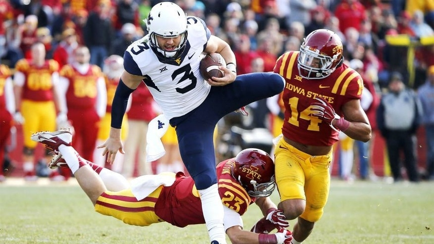 AMES, IA - NOVEMBER 29: Quarterback Skyler Howard #3 of the West Virginia Mountaineers jumps over defensive back Darian Cotton #23 of the Iowa State Cyclones and linebacker Jared Brackens #14 of the Iowa State Cyclones as he scrambles for yards in the first half of play at Jack Trice Stadium on November 29, 2014 in Ames, Iowa. (Photo by David Purdy/Getty Images)