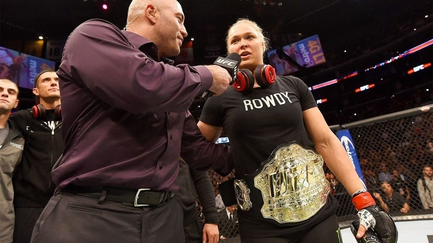 LOS ANGELES, CA - FEBRUARY 28: (L) Joe Rogan interviews Ronda Rousey after her victory over Cat Zingano in their UFC women's bantamweight championship bout during the UFC 184 event at Staples Center on February 28, 2015 in Los Angeles, California. (Photo by Josh Hedges/Zuffa LLC/Zuffa LLC via Getty Images)