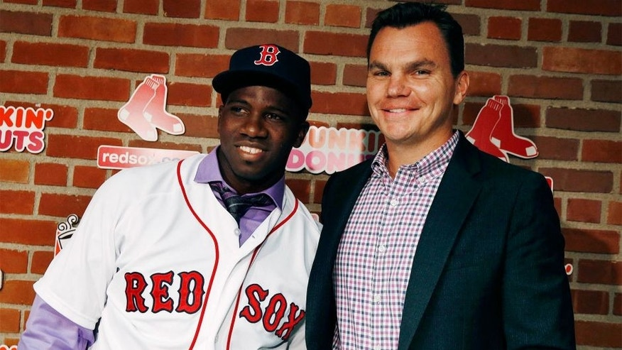 Boston Red Sox general manager Ben Cherington, right, poses with Rusney Castillo after they spoke to reporters following a baseball game between the Red Sox and the Seattle Mariners in Boston, Saturday, Aug. 23, 2014. The Red Sox announced that they signed Castillo, a Cuban defector, to a seven-year contract Saturday. (AP Photo/Michael Dwyer)