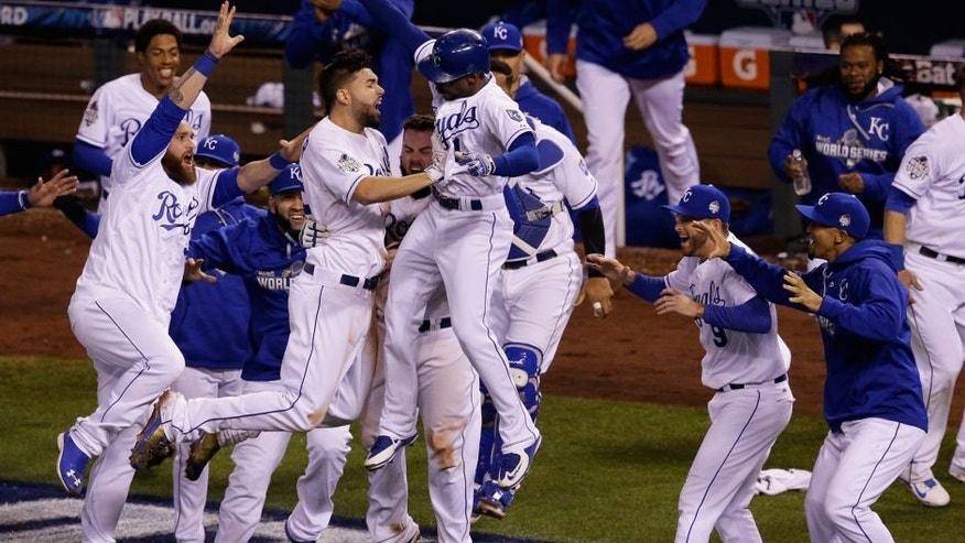 Kansas City Royals players celebrate after Alcides Escobar scored on a sacrifice fly by Eric Hosmer during the 14th inning of Game 1 of the Major League Baseball World Series against the New York Mets Wednesday, Oct. 28, 2015, in Kansas City, Mo. (AP Photo/Orlin Wagner)