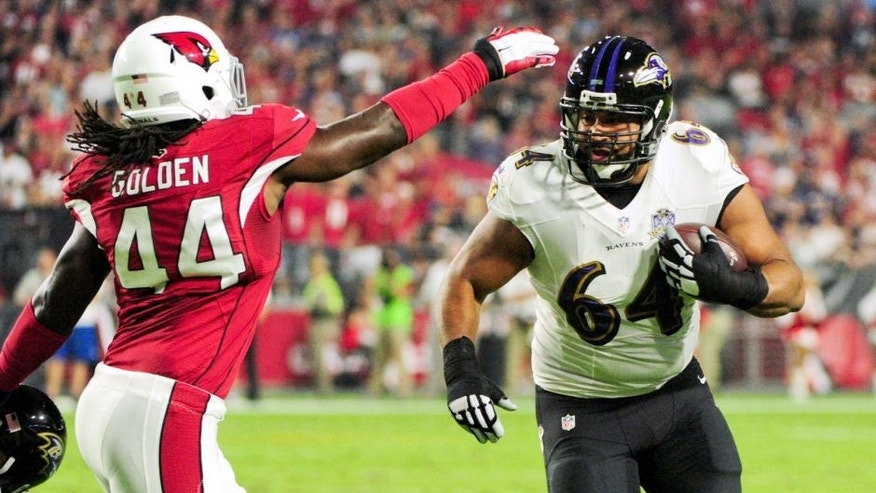 Oct 26, 2015; Glendale, AZ, USA; Baltimore Ravens guard John Urschel (64) carries the ball as Arizona Cardinals outside linebacker Markus Golden (44) defends during the first half at University of Phoenix Stadium. Mandatory Credit: Matt Kartozian-USA TODAY Sports