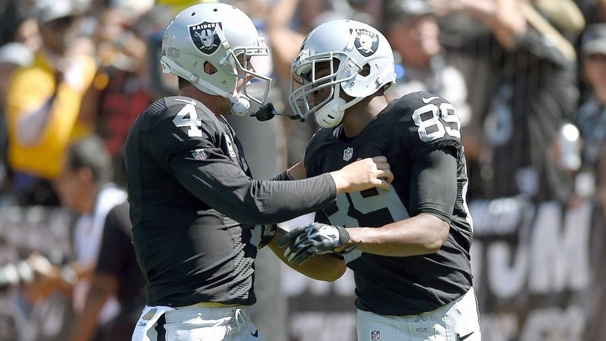OAKLAND, CA - SEPTEMBER 20: Derek Carr #4 of the Oakland Raiders celebrates a touchdown with Amari Cooper #89 of the Oakland Raiders in the first quarter against the Baltimore Ravens at Oakland-Alameda County Coliseum on September 20, 2015 in Oakland, California. (Photo by Thearon W. Henderson/Getty Images)