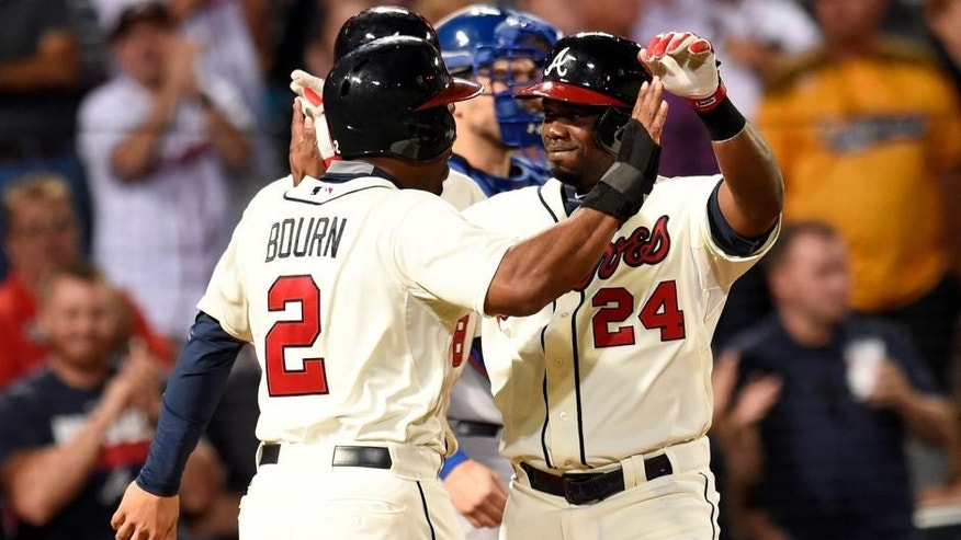 Sep 12, 2015; Atlanta, GA, USA; Atlanta Braves pinch hitter Adonis Garcia (24) reacts with left fielder Michael Bourn (2) after hitting a three run home run against the New York Mets during the eighth inning at Turner Field. Mandatory Credit: Dale Zanine-USA TODAY Sports