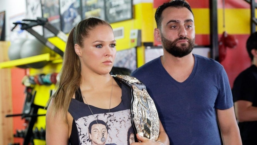 UFC champion Ronda Rousey and her coach Edmond Tarverdyan are seen at a promotional appearance for Rousey's next title defense in Glendale, Calif., Tuesday, Oct. 27, 2015. Rousey isn't sharing her opinion of her mother's sharp criticism of her coach. Tarverdyan also declined to criticize AnnMaria De Mars. Rousey (12-0) will attempt her seventh title defense when she faces former boxing champion Holly Holm at UFC 193 in Melbourne, Australia, on Nov. 15. She has won her previous three fights in 64 combined seconds, establishing herself as the UFC's most dominant champion and the world's most famous MMA fighter.(AP Photo/Nick Ut)
