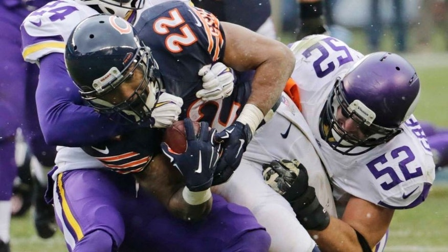 Chicago Bears running back Matt Forte (center) is tackled by Minnesota Vikings cornerback Captain Munnerlyn (left) and linebacker Chad Greenway (right) during the first half.