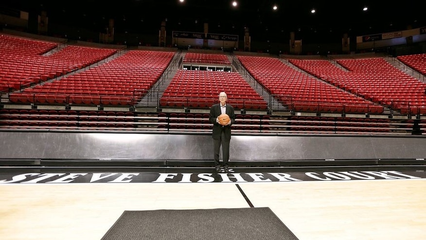 San Diego State basketball coach Steve Fisher poses along the sideline baring his name after a news conference where the floor at the Viejas Arena was named after him Thursday, Oct. 29, 2015, San Diego. (AP Photo/Lenny Ignelzi)