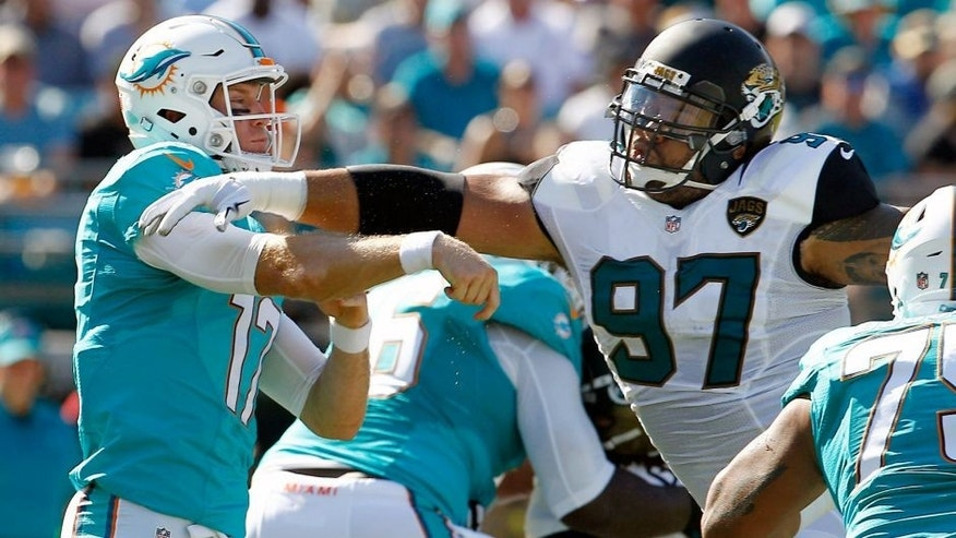 Sep 20, 2015; Jacksonville, FL, USA; Miami Dolphins quarterback Ryan Tannehill (17) drops to throw under pressure from Jacksonville Jaguars defensive tackle Roy Miller (97) during the first quarter of an NFL Football game at EverBank Field. Mandatory Credit: Reinhold Matay-USA TODAY Sports