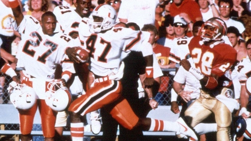TALLAHASSEE, FL - 1987: Michael Irvin #47 of the Miami Hurricanes runs with the ball during the game against the Florida State Seminoles circa 1987 at Doak Campbell Stadium in Tallahassee, Florida. (Photo by Collegiate Images/Getty Images)