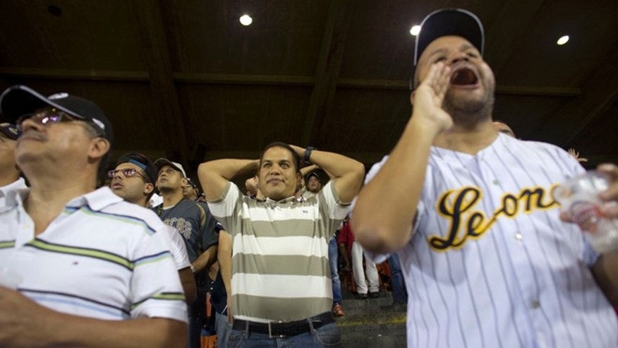 In this Oct. 27, 2015 photo, fans watch a baseball game between the Leones de Caracas and the Navegantes del Magallanes in Caracas, Venezuela. The fact that thousands of Venezuelans so far have been willing to pay the stadiums new ticket prices of up to 2,000 bolivars_ a fifth of the monthly minimum wage_ is a testament to their love for the game. (AP Photo/Ariana Cubillos)