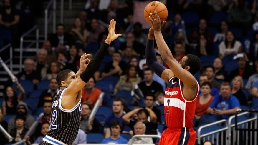 Mar 14, 2014; Orlando, FL, USA; Washington Wizards guard John Wall (2) shoots over Orlando Magic forward Tobias Harris (12) to tie the game and force it into overtime during the fourth quarter at Amway Center. Washington Wizards defeated the Orlando Magic 105-101. Mandatory Credit: Kim Klement-USA TODAY Sports