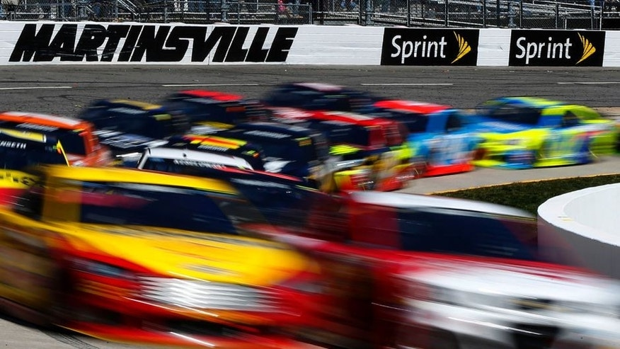 MARTINSVILLE, VA - MARCH 29: Kevin Harvick, driver of the #4 Budweiser/Jimmy John's Chevrolet, and Joey Logano, driver of the #22 Shell Pennzoil Ford, lead the field during the NASCAR Sprint Cup Series STP 500 at Martinsville Speedway on March 29, 2015 in Martinsville, Virginia. (Photo by Matt Sullivan/Getty Images)