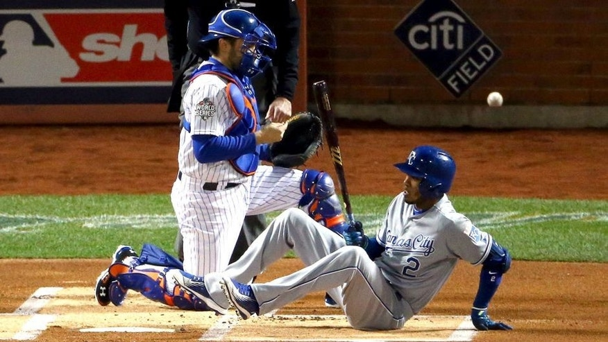 NEW YORK, NY - OCTOBER 30: Alcides Escobar #2 of the Kansas City Royals sits on the field after being brushed back by a pitch as Travis d'Arnaud #7 of the New York Mets controls the ball in the first inning during Game Three of the 2015 World Series at Citi Field on October 30, 2015 in New York City. (Photo by Elsa/Getty Images)