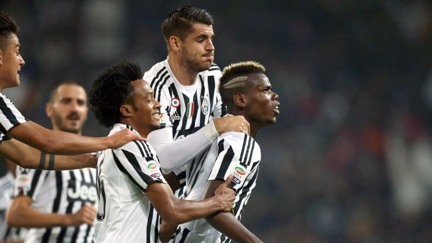 Juventus' French midfielder Paul Pogba (R) celebrates with his teammates after scoring during the Italian Serie A football match Juventus Vs Torino on October 31, 2015 at the Juventus Stadium in Turin. AFP PHOTO / MARCO BERTORELLO (Photo credit should read MARCO BERTORELLO/AFP/Getty Images)