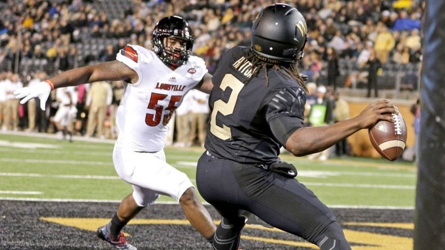 Wake Forest's Kendall Hinton (2) looks to pass from the end zone under pressure from Louisville's Keith Kelsey (55) in the second half of an NCAA college football game in Winston-Salem, N.C., Friday, Oct. 30, 2015. Louisville won 20-19. (AP Photo/Chuck Burton)