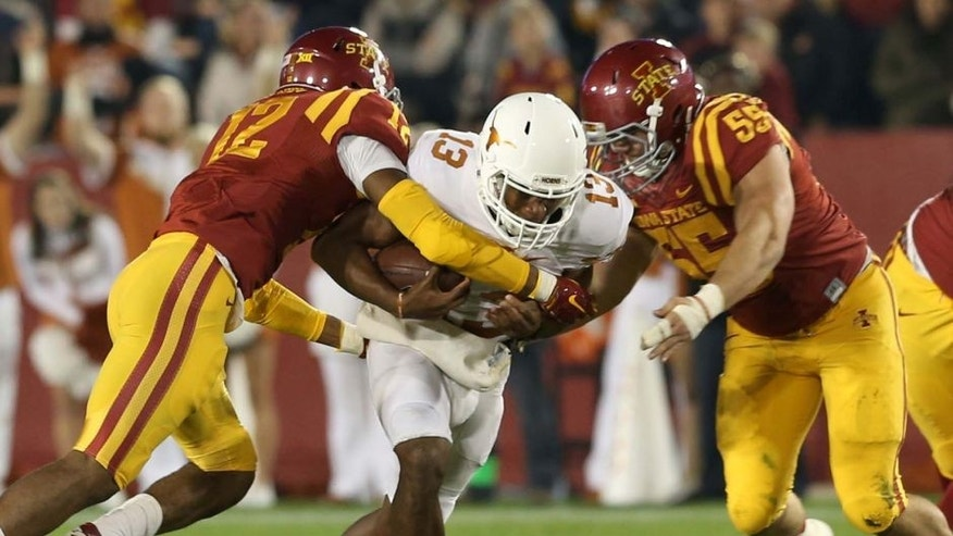 Oct 31, 2015; Ames, IA, USA; Texas Longhorns quarterback Jerrod Heard (13) is tackled by Iowa State Cyclones linebacker Jarnor Jones (12) and Iowa State Cyclones defensive end J.D. Waggoner (55) during the first quarter at Jack Trice Stadium. Mandatory Credit: Reese Strickland-USA TODAY Sports