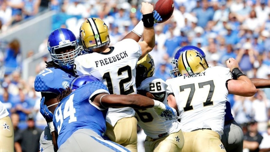Sep 27, 2014; Lexington, KY, USA; Kentucky Wildcats defensive tackle Cory Johnson (67) deflects the pass of Vanderbilt Commodores quarterback Wade Freebeck (12) in the second half at Commonwealth Stadium. Kentucky defeated Vanderbilt 17-7. Mandatory Credit: Mark Zerof-USA TODAY Sports