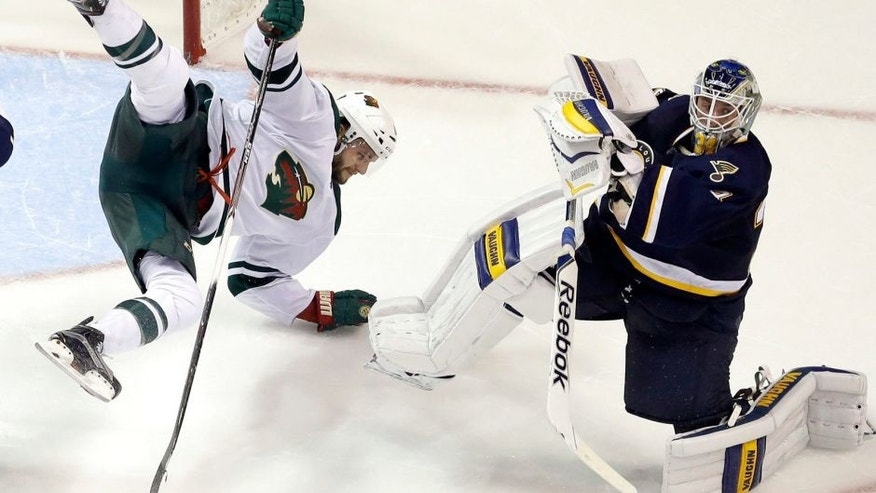 Minnesota Wild's Marco Scandella, left, is sent flying after colliding with St. Louis Blues goalie Jake Allen, right, during overtime of an NHL hockey game Saturday, Oct. 31, 2015, in St. Louis. The Blues won 3-2. (AP Photo/Jeff Roberson)