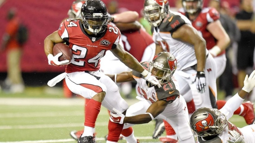 Nov 1, 2015; Atlanta, GA, USA; Atlanta Falcons running back Devonta Freeman (24) breaks a tackle by Tampa Bay Buccaneers cornerback Alterraun Verner (21) during the first half at the Georgia Dome. Mandatory Credit: Dale Zanine-USA TODAY Sports