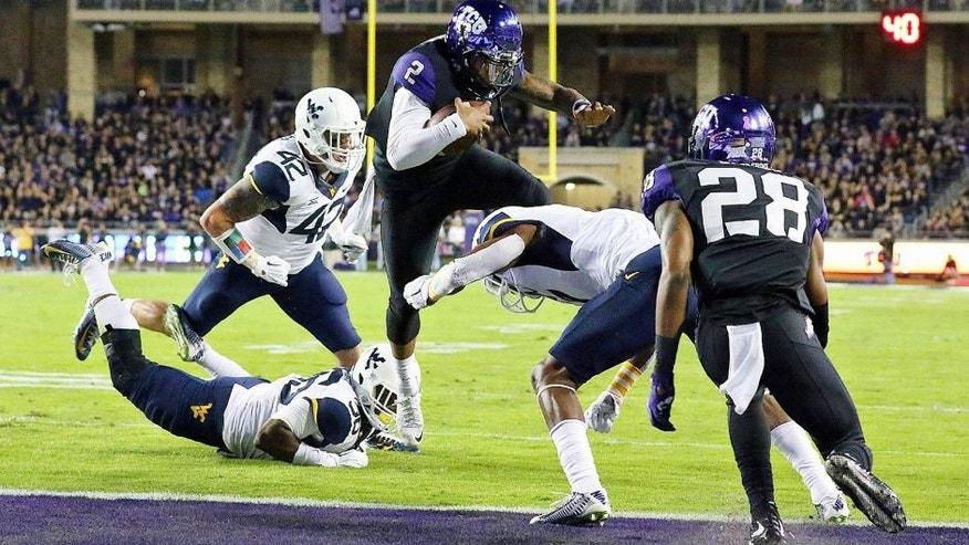 Oct 29, 2015; Fort Worth, TX, USA; TCU Horned Frogs quarterback Trevone Boykin (2) jumps over West Virginia Mountaineers cornerback Daryl Worley (7) as he runs in fro the touchdown during the first quarter of a game at Amon G. Carter Stadium. Mandatory Credit: Ray Carlin-USA TODAY Sports