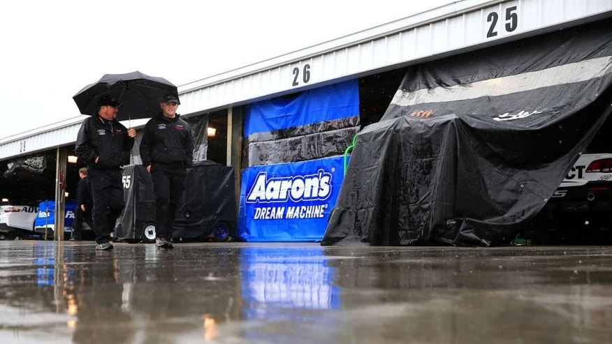 MARTINSVILLE, VA - MARCH 27: Crew members walk through the garage area as it rains prior to practice for the NASCAR Sprint Cup Series STP 500 at Martinsville Speedway on March 27, 2015 in Martinsville, Virginia. (Photo by Daniel Shirey/Getty Images)