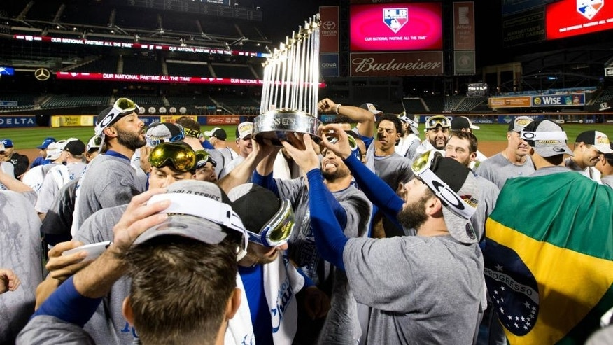 NEW YORK, NY - NOVEMBER 1: Members of the Kansas City Royals hoist up the Commissioner's Trophy on the field after defeating the New York Mets in Game 5 of the 2015 World Series at Citi Field on Sunday, November 1, 2015 in the Queens borough of New York City. (Photo by Rob Tringali/MLB Photos via Getty Images)