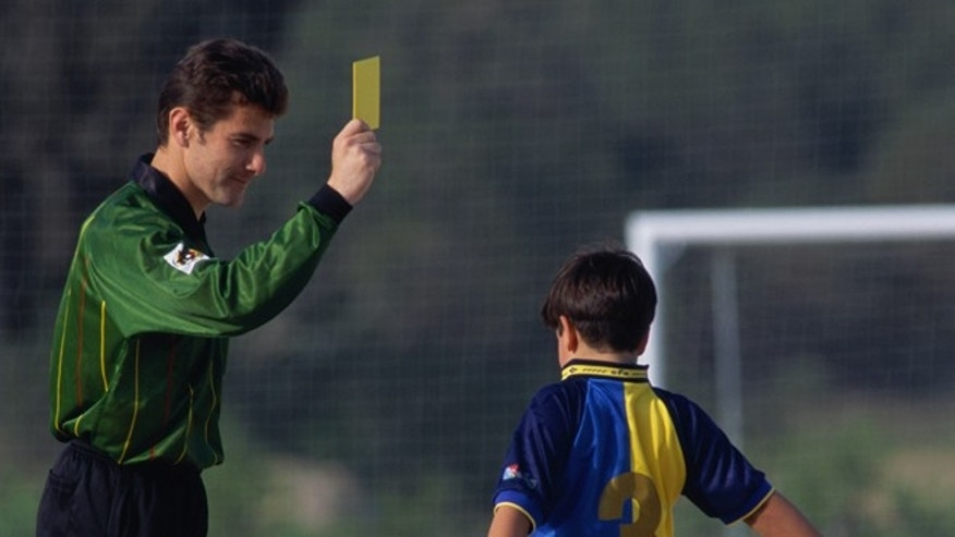 Model Released: Soccer referee holding yellow card in front of boy (8-10) (Photo by Pascal Rondeau/Getty Images)