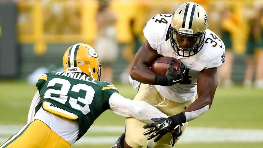 Sep 3, 2015; Green Bay, WI, USA; New Orleans Saints running back Tim Hightower (34) tries to break a tackle by Green Bay Packers cornerback Damarious Randall (23) in the first quarter at Lambeau Field. Mandatory Credit: Benny Sieu-USA TODAY Sports