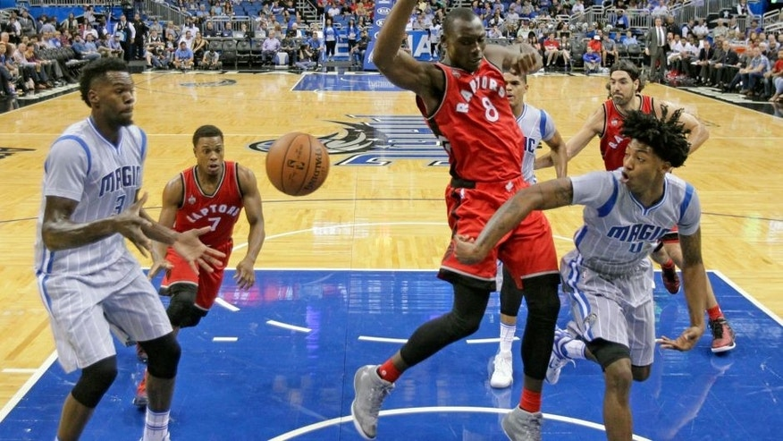 Orlando Magic guard Elfrid Payton (4) passes the ball around Toronto Raptors forward Bismack Biyombo (8) to center Dewayne Dedmon, left, during the first half of an NBA basketball game, Friday, Nov. 6, 2015, in Orlando, Fla. (AP Photo/John Raoux)