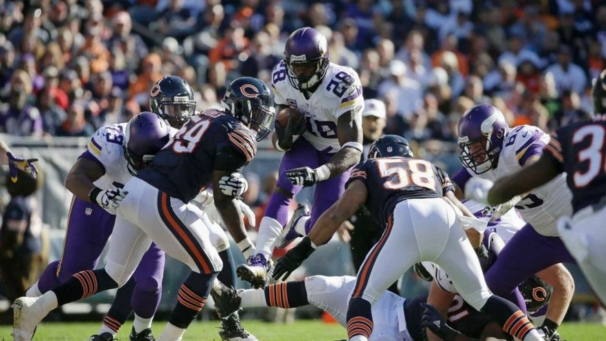 Minnesota Vikings running back Adrian Peterson leaps over players as he carries the ball against Chicago Bears defenders during the first half of an NFL football game Sunday, Nov. 1, 2015, in Chicago.