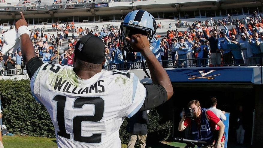 Oct 25, 2014; Charlottesville, VA, USA; North Carolina Tar Heels quarterback Marquise Williams (12) celebrates while leaving the field after the Tar Heels' game against the Virginia Cavaliers at Scott Stadium. The Tar Heels won 28-27. Mandatory Credit: Geoff Burke-USA TODAY Sports