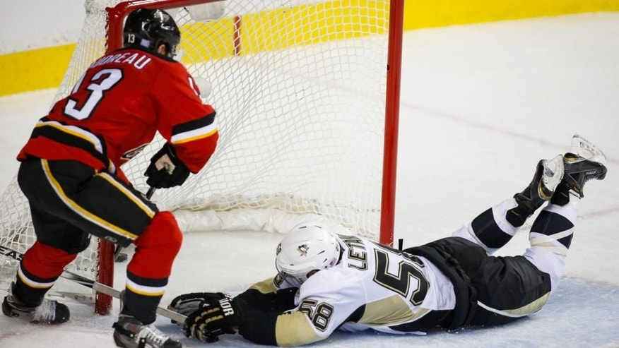 Pittsburgh Penguins' Kris Letang, right, attempts to block a goal from Calgary Flames' Johnny Gaudreau during third period NHL hockey action, in Calgary, on Saturday, Nov. 7, 2015. (Jeff McIntosh/The Canadian Press via AP)