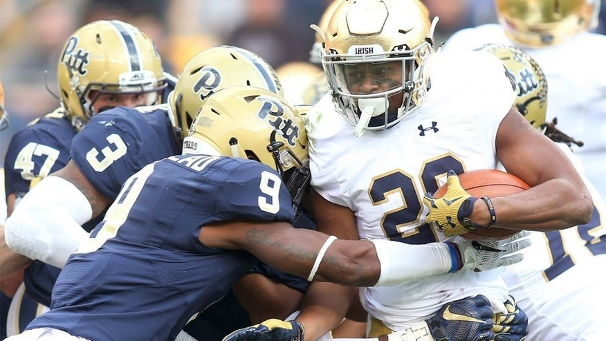 Nov 7, 2015; Pittsburgh, PA, USA; Notre Dame Fighting Irish running back C.J. Prosise (20) carries the ball as Pittsburgh Panthers linebacker Nicholas Grigsby (3) and defensive back Jordan Whitehead (9) defend during the first quarter at Heinz Field. Mandatory Credit: Charles LeClaire-USA TODAY Sports