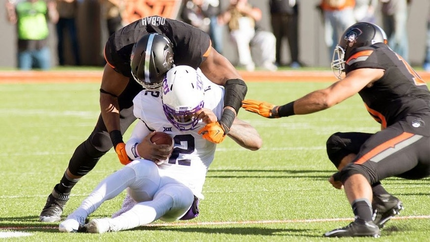 Nov 7, 2015; Stillwater, OK, USA; TCU Horned Frogs quarterback Trevone Boykin (2) tackled by Oklahoma State Cowboys defensive end Emmanuel Ogbah (38) during the first quarter at Boone Pickens Stadium. Mandatory Credit: Rob Ferguson-USA TODAY Sports