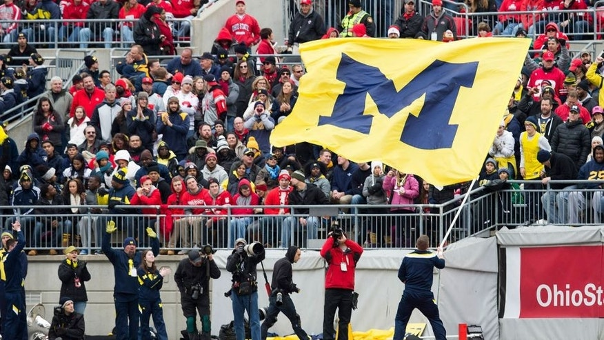 Nov 29, 2014; Columbus, OH, USA; A Michigan Wolverines cheerleader waves the Michigan flag in front of Ohio State Buckeyes fans at Ohio Stadium. Ohio State won the game 42-28. Mandatory Credit: Greg Bartram-USA TODAY Sports