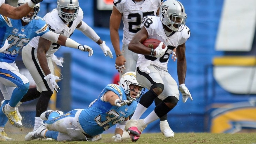 Oct 25, 2015; San Diego, CA, USA; Oakland Raiders strong safety T.J. Carrie (38) returns a punt as San Diego Chargers running back Danny Woodhead (39) defends during the third quarter at Qualcomm Stadium. Mandatory Credit: Jake Roth-USA TODAY Sports