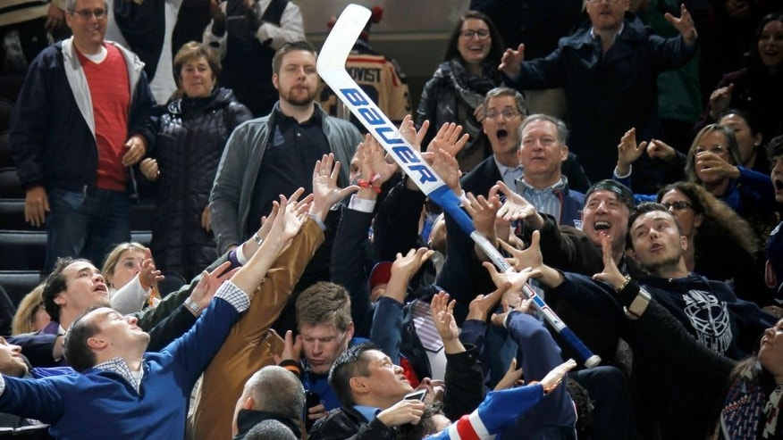 NEW YORK, NY - NOVEMBER 10: Fans battle the stick of Henrik Lundqvist #30 of the New York Rangers (not pictured) after he throws it into the crowd following his shutout against the Carolina Hurricanes at Madison Square Garden on November 10, 2015 in New York City. (Photo by Jared Silber/NHLI via Getty Images)