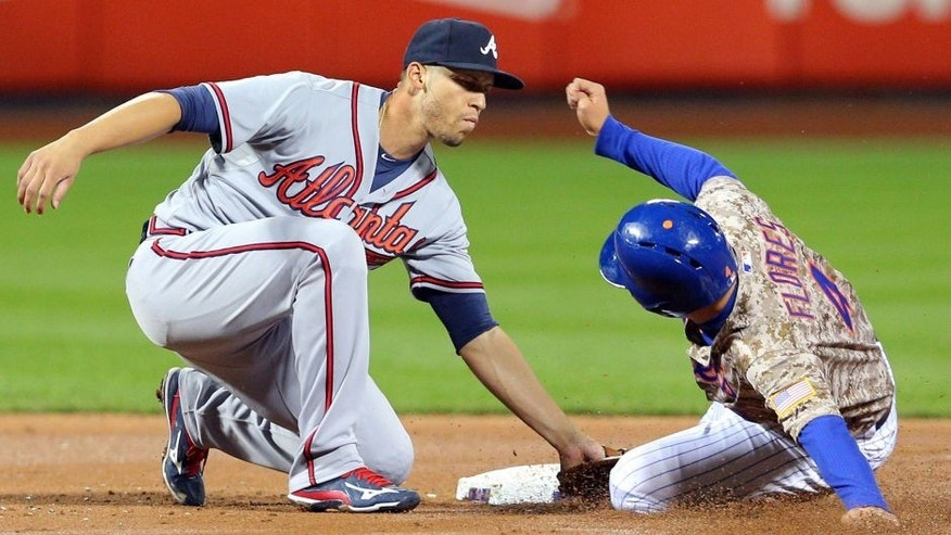 Sep 21, 2015; New York City, NY, USA; Atlanta Braves shortstop Andrelton Simmons (19) tags out New York Mets shortstop Wilmer Flores (4) on a steal attempt during the second inning at Citi Field. Mandatory Credit: Brad Penner-USA TODAY Sports