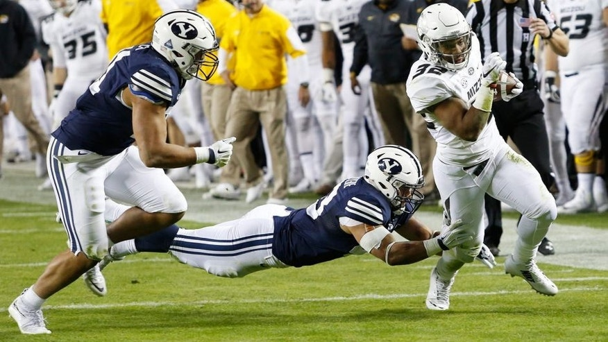 Missouri running back Russell Hansbrough, right, slips past BYU linebackers Jherremya Leuta-Douyere, center, and Harvey Langi, left, in the first half of a college football game at Arrowhead Stadium, Saturday, Nov. 14, 2015, in Kansas City, Mo. (AP Photo/Colin E. Braley)
