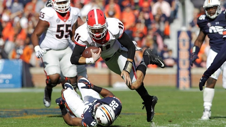 Nov 14, 2015; Auburn, AL, USA; Georgia Bulldogs quarterback Greyson Lambert (11) stumbles past Auburn Tigers corner back Devin Gillespie (26) during the third quarter at Jordan Hare Stadium. The Bulldogs beat the Tigers 20-13. Mandatory Credit: John Reed-USA TODAY Sports